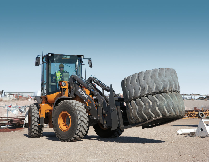 A case loader hauling two large used heavy equipment tires