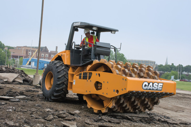 A Case compactor rolling over a dirt mound