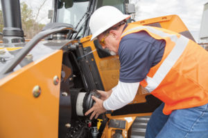 man changing the air filter in a backhoe